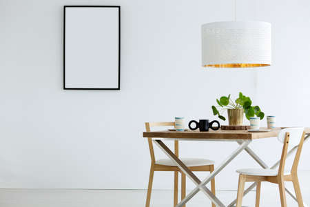 Mockup of white, empty poster in bright dining room interior with lamp above table and chairs