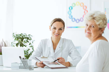 Smiling doctor sitting at her office with balanced diet recommendation for her patient with overweight Stock Photo