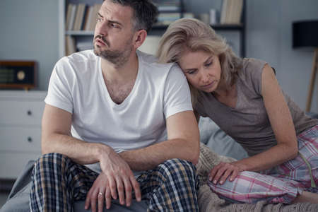 Unhappy husband and sad wife sitting together in the bedroom. Difficult marriage concept
