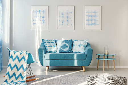 White and blue blanket on rocking chair in bright living room interior with dyed cushions on turquoise sofa