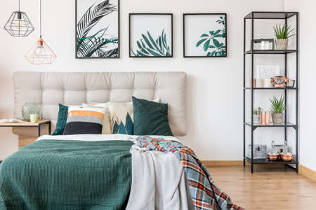 Close-up of a double bed covered with blankets and cushions standing next to a metal shelf in bedroom interior Stock Photo