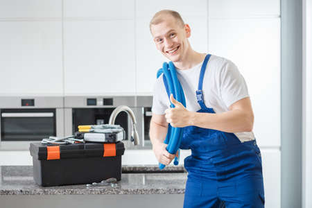 Smiling plumber giving a thumbs-up to a customer standing next a tool box in a kitchen
