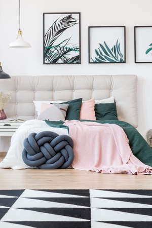 King-size bed with a knot pillow in front and botanical posters on the wall in a bedroom interior