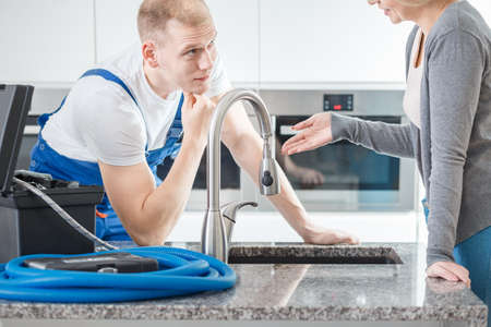 Focused plumber talking to a client over a sink in a kitchen