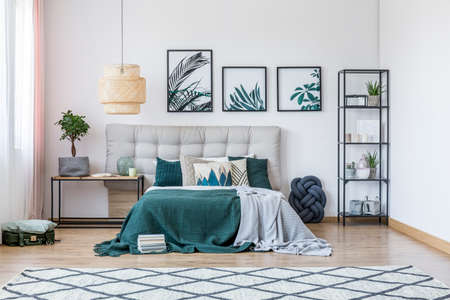 Modern, white bedroom interior with patterned carpet and double bed standing next to a table Stock Photo