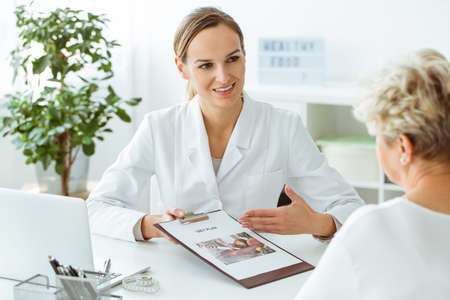 Female doctor sitting by the desk with her patient and introducing healthy diet Banque d'images