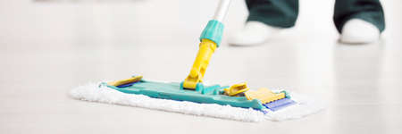 Close-up of a cleaner wiping a white floor with a mop