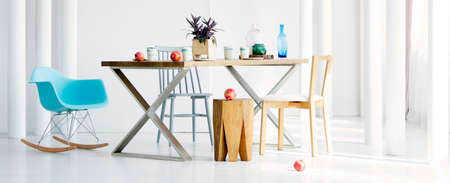 Wooden stool and blue rocking chair at the table in dining room interior with pomegranates and tubes Standard-Bild - 97183697