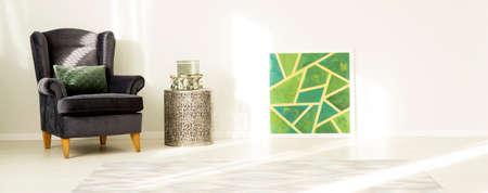 Green jam à côté de la table en métal avec des boîtes dans l & # 39 ; intérieur de la chambre avec un fauteuil sombre Banque d'images - 97183709