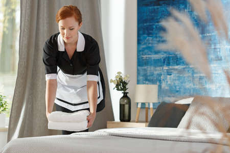 Chambermaid putting towels on a bed in a hotel room Stock Photo