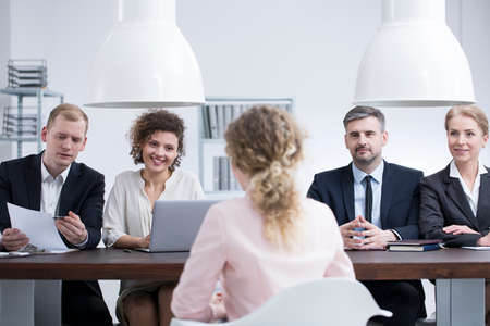 Young businesswoman discussing her resume with a team of recruiters in a company office