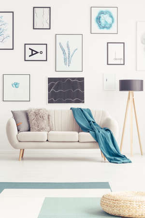 Blue blanket on a settee next to a lamp in living room interior with pouf and gallery of posters