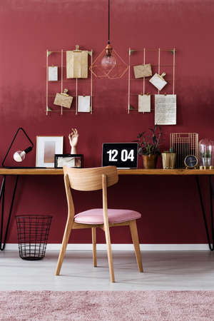 Wooden chair at desk with laptop against dark pink wall with notes in womans workspace interior