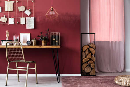 Pink curtain and logs of wood next to a desk with clock and metal chair in womans workspace interior
