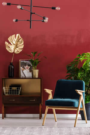 Green, wooden armchair next to a cupboard with gold leaf in red living room interior with lamp Foto de archivo