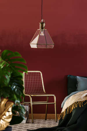 Lamp above green chair next to bed in red, luxurious bedroom interior