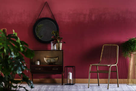 Gold chair next to a cabinet with plant against red wall with mirror in living room interior with a candle