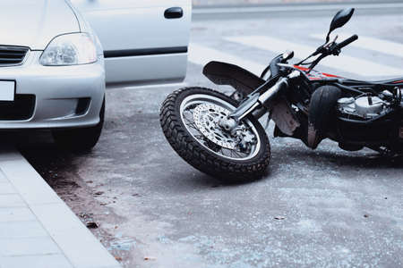Motorcycle lying on the road and car standing with open door after a collision