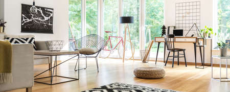 Basket on the table and pouf on the wooden floor in spacious living room with chair at desk, bike and lamp