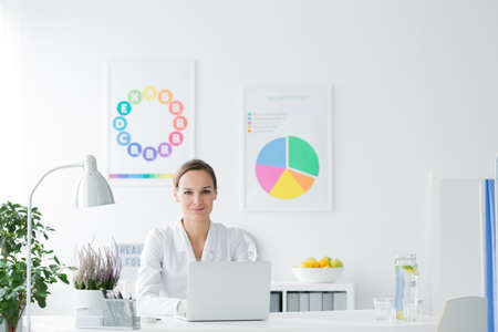 Smiling nutritionist sitting at desk with laptop in white office with posters Zdjęcie Seryjne