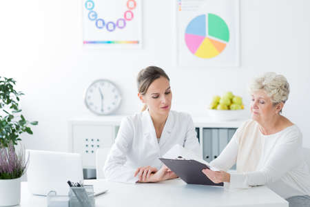 Dietician showing personalized diet plan to diabetic patient in the health center Stock Photo