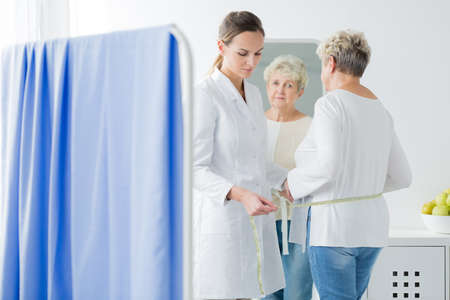 Dietician measuring body circuit of patient with overweight Stock Photo