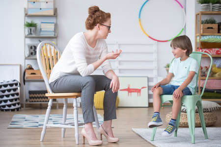 Smiling child on a mint chair talking to a speech therapist at school Stock Photo