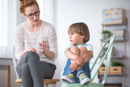 Sad boy with Asperger syndrome during therapy with kid therapist