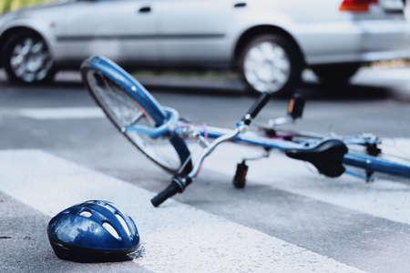Helm und Fahrrad liegen auf der Straße, nachdem ein Auto einen Radfahrer auf einem Fußgängerüberweg getroffen hat Standard-Bild - 97415380