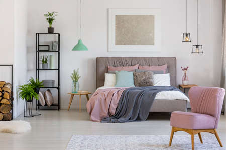 Pink armchair and double bed in elegant bedroom interior with silver painting and mint lamp