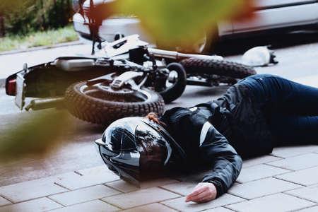 Mujer motociclista acostada inconsciente en el pavimento después de tener un accidente en la carretera Foto de archivo