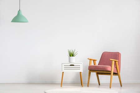fauteuil rose et table en bois sur le mur vide dans l & # 39 ; intérieur de salon simple