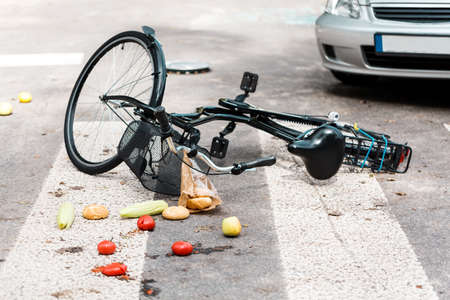 Fresh vegetables and bread rolls scattered on the road after an accident with bike hit by a car on pedestrian crossing