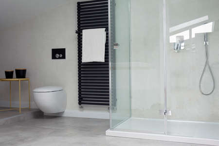 Glass Shower In Bright Bathroom Interior With Toilet And White Towel On  Black Heater Stock Photo