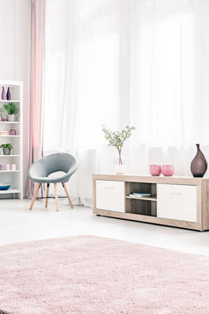 Grey armchair next to a wooden cupboard in bright, pastel living room interior with pink carpet