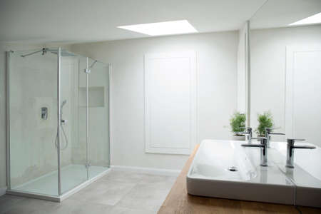 White bathroom interior with glass shower and window on the attic