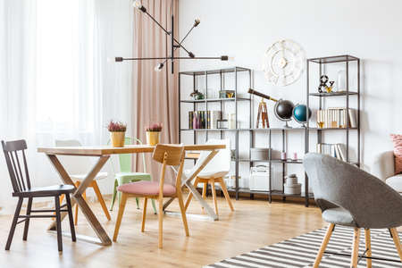 Black lamp above wooden dining table in open space apartment interior with decorations on a metal rack Фото со стока