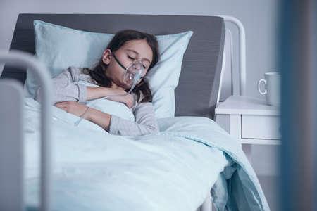 彼女の顔に酸素マスクを持つ病院のベッドに横たわっている若い女の子