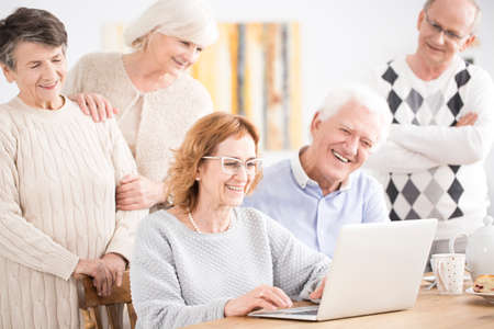 A group of five elders looking and smiling at a laptop during a video conference with relatives Zdjęcie Seryjne