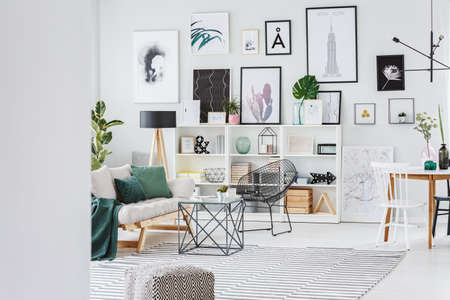 Bright, stylish living room interior with grey sofa, gallery and decor