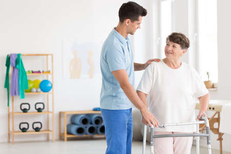 Caring physiotherapist supporting an elderly woman with a walking frame Stock fotó