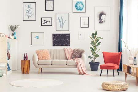 Poef, rond kleed en rode fauteuil in kleurrijk woonkamerinterieur met beige bank en posters Stockfoto