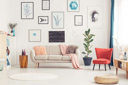 Pouf, round rug and red armchair in colorful living room interior with beige sofa and posters Stockfoto