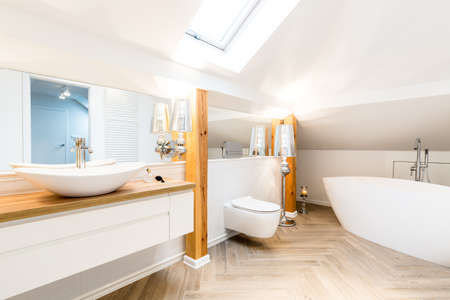 White washbasin in modern bathroom interior with bathtub and toilet on the attic Zdjęcie Seryjne