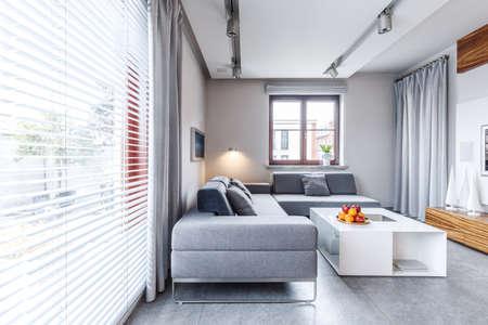 モダンなリビングルームのインテリアにオレンジを持つ白いテーブルの近くの灰色のコーナーソファ
