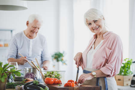 Smiling senior woman cutting tomatoes and grandfather stirring soup