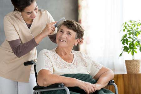 Caring pleurer peigner les cheveux d & # 39 ; un patient aîné dans une maison de soins infirmiers Banque d'images - 97184394