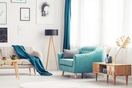 Armario de madera junto al sillón azul en el acogedor salón interior con sofá beige Foto de archivo