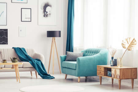 Wooden cupboard next to blue armchair in cozy living room interior with beige settee