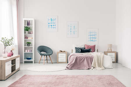 Grey armchair next to bed with pink bedsheets in pastel bedroom interior with blue posters
